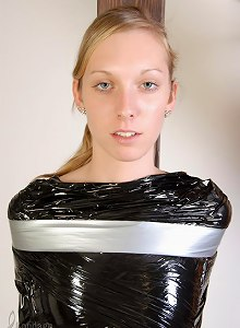 Young 18yo girl standing wrapped in plastic, taped to pole