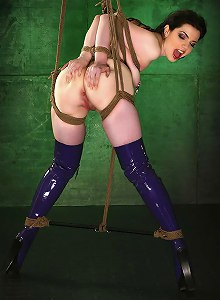 High-booted, tattooed brunette Nicotine gets tied up, suspended, and filled in all her holes with dildos