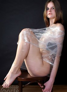 Young 18yo girl wrapped in plastic, exposing shaved pussy