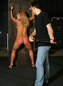 Amazing blonde is locked to the wooden sheet and whipped hard