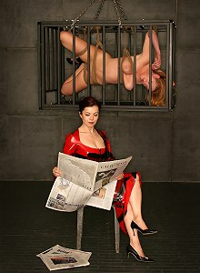 Busty blonde caged in the Cell watching by mistress in red dress