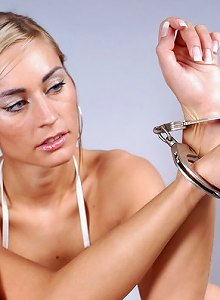 Blond chick in sexy underwear chained and cuffed on the table